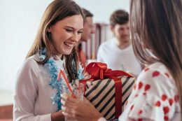 Girl gives a gift to her friend during the new year party
